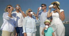 Happy family drinking tea and showing thumbs up outdoor - stock footage
