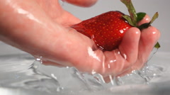 Hand pick up strawberry from water Stock Footage
