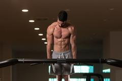 Young Bodybuilder Exercising Triceps Doing Dips on Bar Stock Photos