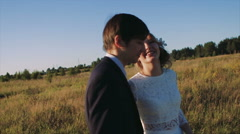 Bride and Groom Kissing at Sunset in Field Stock Footage