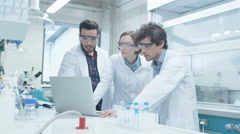 Group of Multiethnic Students in Coats using Laptop in Laboratory Stock Footage