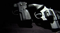 Several guns looking ominous in the shadows as the camera dollies across them.  Stock Footage