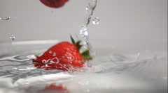 Three strawberries drop into water Stock Footage