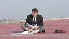 Young businessman in anger, rips the paper sitting on the pavement - stock footage