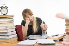 Student sadly looking at turning the pages in a folder at the desk among the  - stock photo