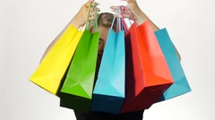 Beautiful blonde holds a lot of different color packages in hands and smiling Stock Footage