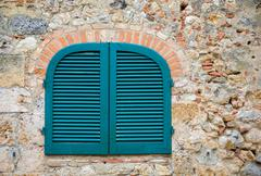 Blue Shutters in an Ancient Tuscan Stone Wall - stock photo