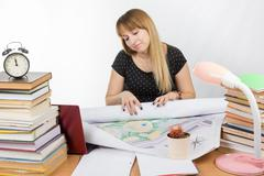 Girl design student sitting at a desk and is tired deploys a large drawing - stock photo