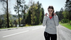 Beautiful young woman runner athlete insert her earphones during training Stock Footage