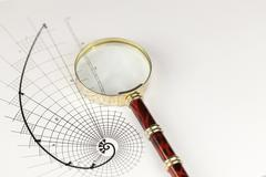 Magnifying glass & drawing of the golden section Stock Photos