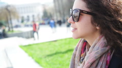 happy young woman in glasses sits on a bench in the city - stock footage