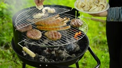 A young woman puts mushrooms on the grill, with sound. Stock Footage