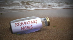 breaking news written on a message washed ashore - stock footage