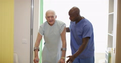 4K Caring medical worker helping elderly man to walk with crutches Stock Footage