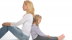 Little girl and mother sit back to back Stock Footage