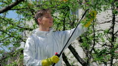 Handsome guy spraying chemicals in the garden Stock Footage