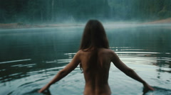 Beautiful naked fairy or mermaid with long dark hair in the mystical foggy - stock footage