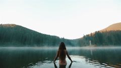 Beautiful naked fairy or mermaid with long dark hair in the mystical foggy Stock Footage