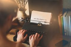 New life chapter one against young woman using typewriter - stock photo