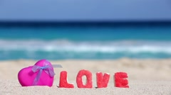 One pink heart shape and sign LOVE made of sweet letters on tropical beach Stock Footage