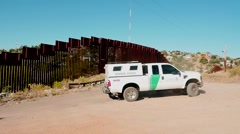 A US Border Patrol truck drives off to investigate the fence - stock footage