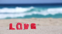 Sign LOVE made of sweet letters on sandy  beach Stock Footage