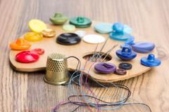 Buttons, thimble, needle and thread on the palette Stock Photos