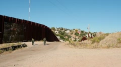Border Patrol agents investigating the fence line Stock Footage