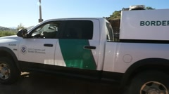 US Border Patrol trucks park near the fence by the Mexican border Stock Footage