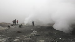 Group of tourists photographed smoking fumarole in crater active volcano Stock Footage