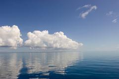 Clouds above calm ocean. Stock Photos