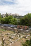 Metro train-line through Athens Ancient Agora with Acropolis in the backgroun - stock photo
