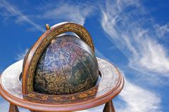 Mounted Retro World Globe Against Blue Cloudy Sky Stock Photos