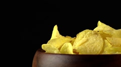 Rotating potato chips on black background Stock Footage