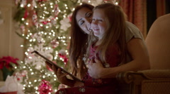 Medium shot of mother and daughter using digital tablet at Christmas / Cedar Stock Footage