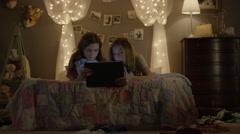 Medium shot of teenage girls sharing digital tablet in bedroom / Cedar Hills, Stock Footage