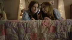 Medium shot of teenage girls talking on cell phone at sleepover / Cedar Hills, Stock Footage
