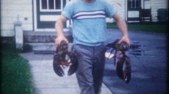3299 man holds two large lobsters for family dinner - vintage film home movie Stock Footage