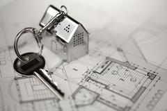 Key with keychain in the form of a silver-colored house on a background of ar Stock Photos