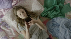 High angle close up of teenage girl using cell phone on bed / Cedar Hills, Utah, Stock Footage