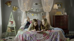 Medium shot of teenage girls doing homework on bed / Cedar Hills, Utah, United Stock Footage