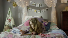 Medium shot of teenage girl doing homework on bed / Cedar Hills, Utah, United Stock Footage