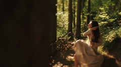 Gentle young girl sitting barefoot in the carpathian woods and combing her Stock Footage