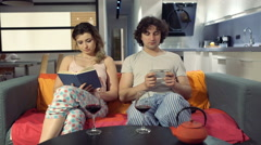 Woma finish reading book and yawning while her boyfriend using smartphone Stock Footage