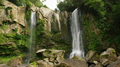 Wide low angle slow motion shot of rocky waterfalls / Dominical, Punta Arenas, Stock Footage