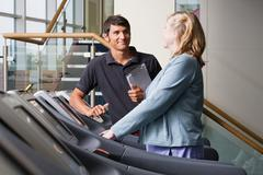 A personal trainer and woman on a treadmill - stock photo