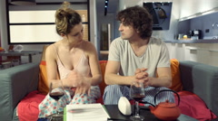 Couple in pajamas sitting on the sofa and quarrelling with each other Stock Footage