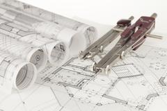 rolls of architecture blueprints, house plans &  compasses - stock photo