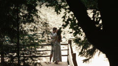 Side view of happy young couple standing on edge of pier by lake in mountains Stock Footage