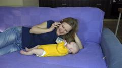 Mom give newborn girl bottle of milk. Woman talk phone. 4K Stock Footage